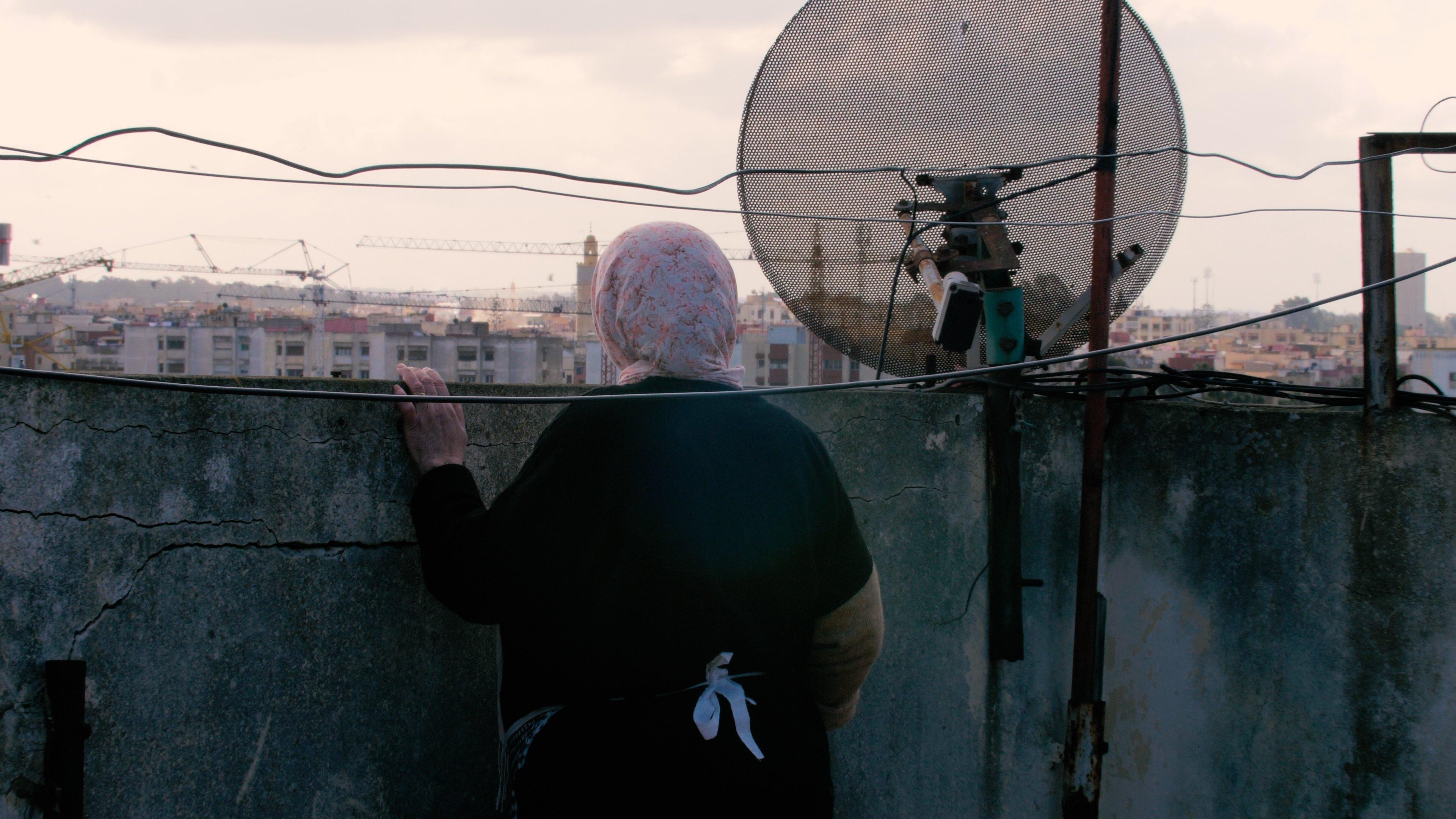 Une femme qui regarde la ville en haut d'un terrace