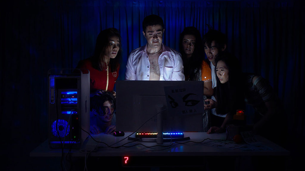 People gathered in front of a computer
